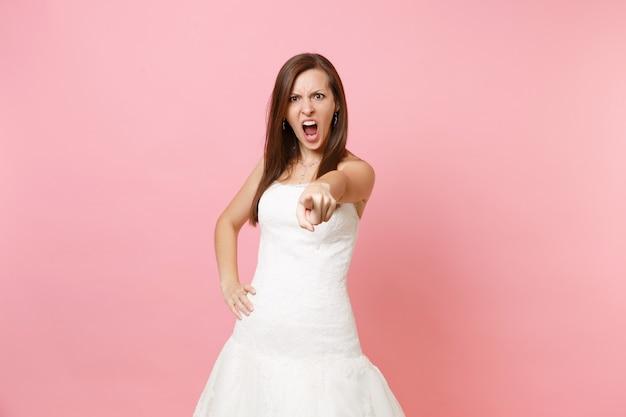 Porträt einer strengen wütenden frau im weißen kleid, die schreiend schreiend mit dem zeigefinger nach vorne zeigt
