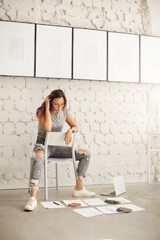 Porträt einer studentin des modedesigns, die in ihrem eigenen studio oder auf ihrem campus arbeitet und textilmuster und -skizzen betrachtet.