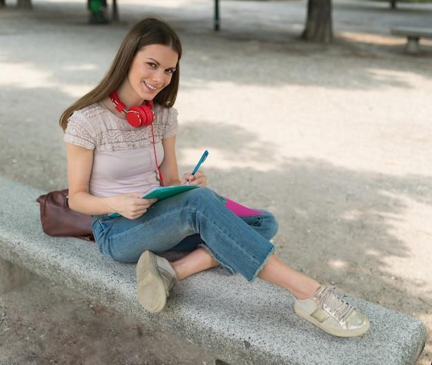 Porträt einer studentin, die in einem park vor der schule studiert