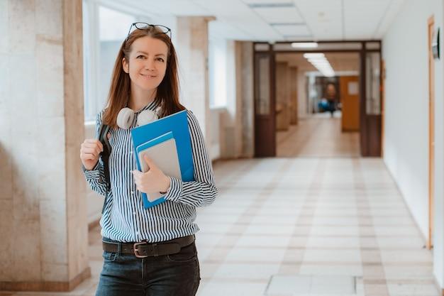 Porträt einer studentin im flur der universität mit büchern