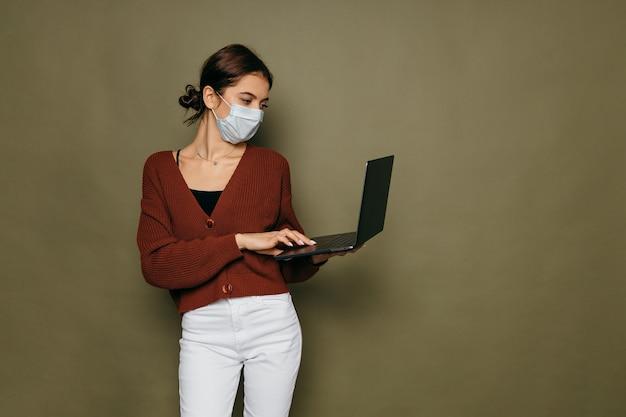 Porträt einer studentin in einer schutzmaske mit einem laptop auf einem grünen hintergrund. hochwertiges foto