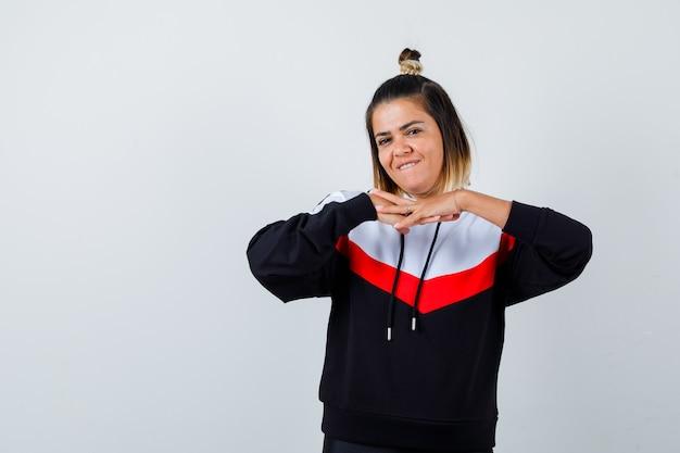 Porträt einer süßen dame, die die hände unter dem kinn hält, im hoodie auf die lippe beißt und fröhliche vorderansicht sieht
