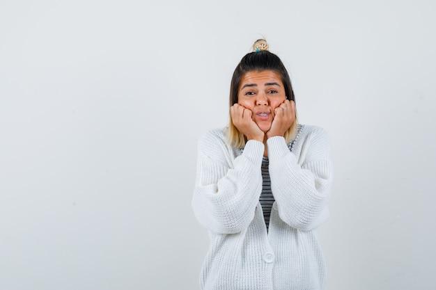 Porträt einer süßen dame, die wangen an den händen in t-shirt, strickjacke lehnt und aufgeregt aussieht