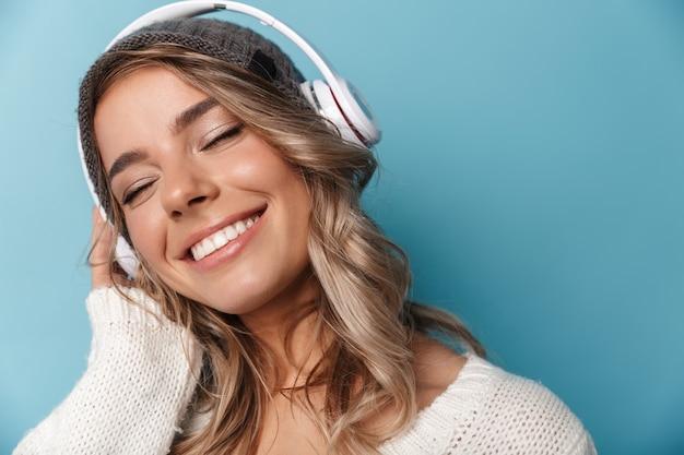 Porträt einer süßen, erfreuten frau in strickmütze, die lächelt und kopfhörer verwendet, die über blauer wand isoliert sind?