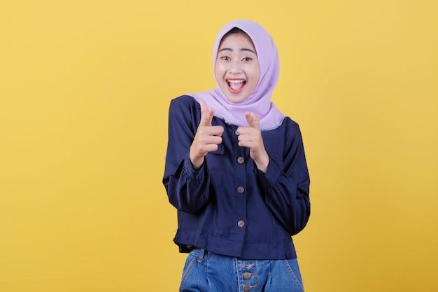 Porträt einer süßen frau, die auf sie in legerem tuch zeigt, das hijab auf isoliertem gelbem hintergrund trägt