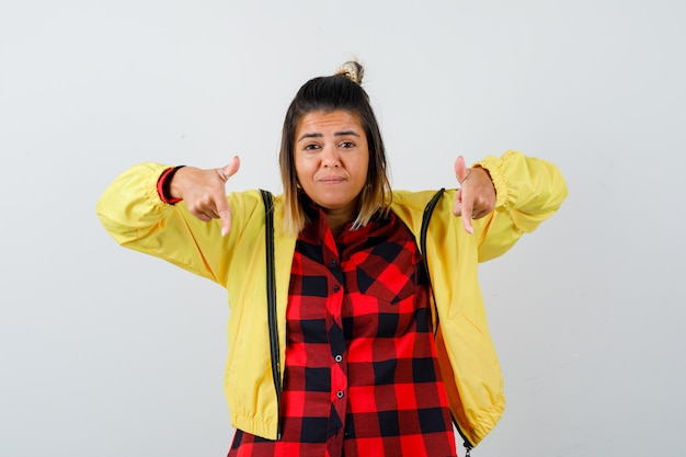 Porträt einer süßen frau, die in hemd, jacke und unentschlossener vorderansicht nach unten zeigt
