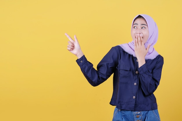 Porträt einer süßen frau, die in legerem tuch mit hijab auf isoliertem gelbem hintergrund nach oben zeigt