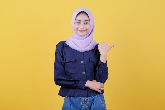 Porträt einer süßen frau, die mit dem daumen in legerem tuch zeigt, das hijab auf isoliertem gelbem hintergrund trägt