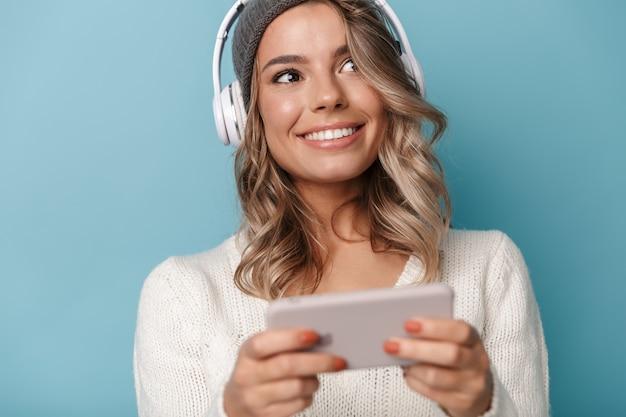 Porträt einer süßen, fröhlichen frau in strickmütze mit kopfhörern und handy isoliert über blauer wand