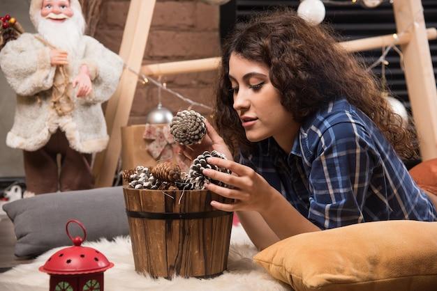 Porträt einer süßen jungen frau, die in einen hölzernen korb mit tannenzapfen schaut