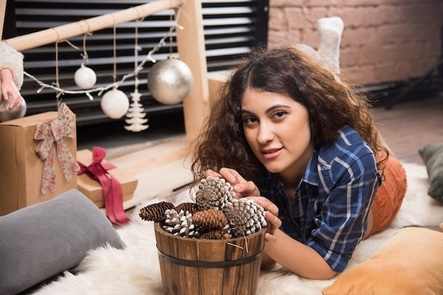 Porträt einer süßen jungen frau, die mit einem holzkorb aus tannenzapfen posiert