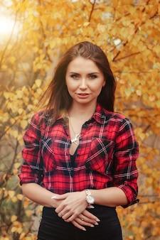 Porträt einer süßen jungen frau mit slawischem aussehen in freizeitkleidung im herbst, auf dem land vor dem hintergrund eines herbstparks. hübsche frau, die im goldenen herbst im wald geht. platz kopieren