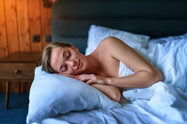 Porträt einer süßen jungen schlafenden frau auf einem weißen weichen leinen an einem hotelzimmerbett