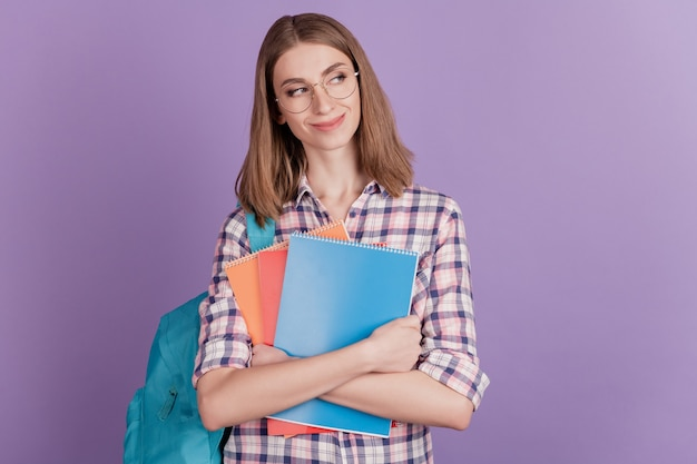 Porträt einer süßen jungen studentin, die ein notebook in ihrer handtasche hält, sieht leer aus, isoliert auf violettem farbhintergrund