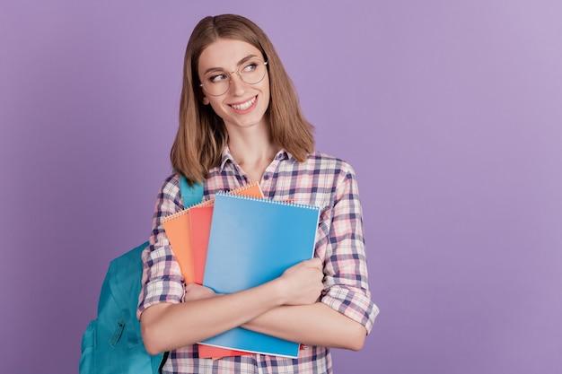 Porträt einer süßen jungen studentin, die ein notizbuch in ihrer handtasche hält, neugieriger blick leerer raum einzeln auf violettem farbhintergrund
