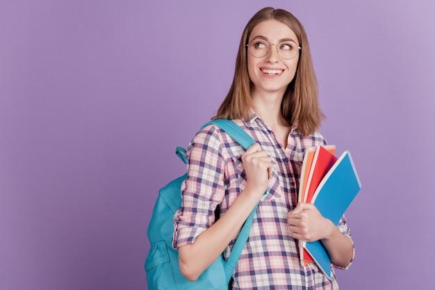 Porträt einer süßen jungen studentin, die ein notizbuch in ihrer handtasche hält, studiere den traum isoliert auf violettem farbhintergrund