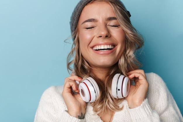 Porträt einer süßen lustigen frau in strickmütze, die lacht und kopfhörer verwendet, die über blauer wand isoliert sind?