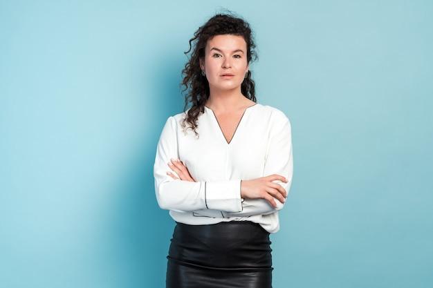 Porträt einer süßen positiven frau mit lockiger frisur und in weißer bluse, die mit verschränkten armen, freundlichem aussehen und charmantem lächeln steht. indoor-studioaufnahme auf blauem hintergrund isoliert