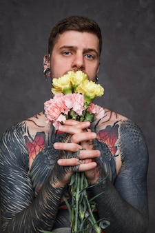 Porträt einer tätowierung und des durchbohrten jungen mannes, die gartennelkenblume in den verbundenen händen hält
