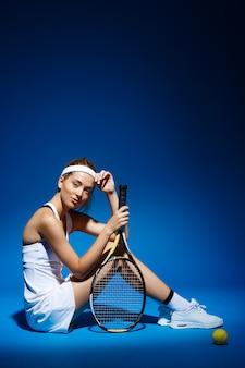 Porträt einer tennisspielerin mit schläger und ball auf dem boden sitzend
