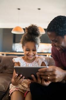 Porträt einer tochter und eines vaters, die ein digitales tablett verwenden, während sie zu hause bleiben