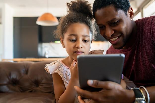 Porträt einer tochter und eines vaters, die spaß zusammen haben und mit digitalem tablett zu hause spielen. monoparentales konzept.