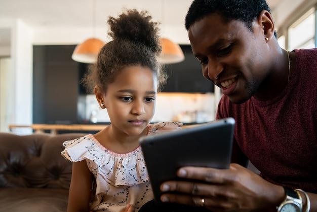 Porträt einer tochter und eines vaters, die spaß zusammen haben und mit digitalem tablett zu hause spielen