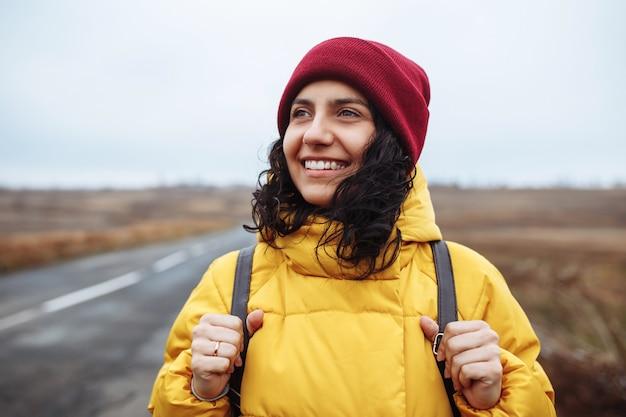 Porträt einer touristin mit einem rucksack, der gelbe jacke und roten hut trägt, steht auf der straße.