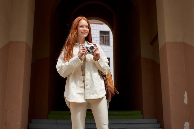 Porträt einer touristischen rothaarigen frau, die ein foto der architektur auf einer retro-filmkamera macht