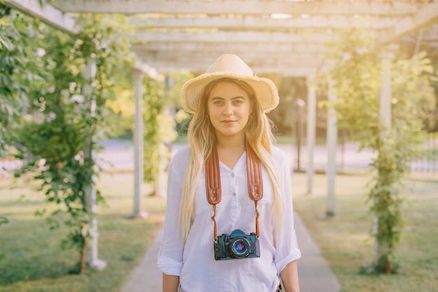 Porträt einer tragenden kamera der jungen frau um den hals, der im garten steht