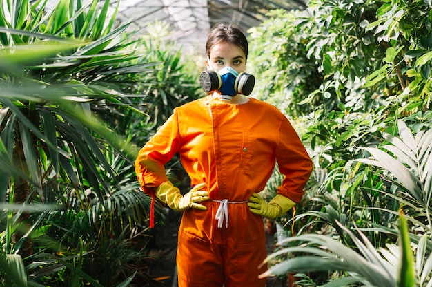 Porträt einer tragenden verschmutzungsmaske des weiblichen gärtners, die im gewächshaus steht