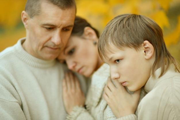 Porträt einer traurigen dreiköpfigen familie in der natur