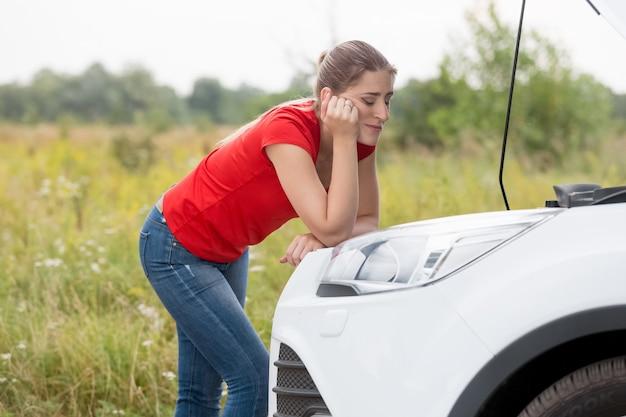 Porträt einer traurigen frau, die auf einem kaputten auto auf die landschaft schaut