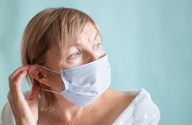 Porträt einer traurigen frau, die eine medizinische maske wegen der coronavirus-epidemie trägt