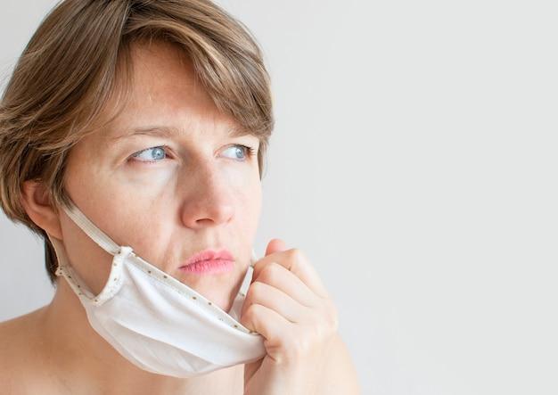 Porträt einer traurigen frau, die eine medizinische maske wegen der coronavirus-epidemie trägt.