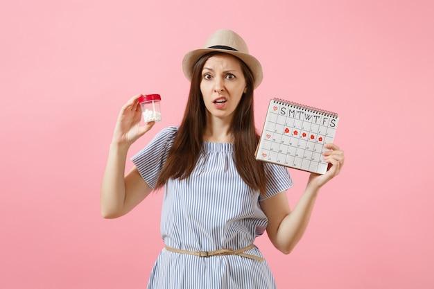 Porträt einer traurigen frau im blauen kleid, die weiße flasche mit pillen hält, kalender für weibliche perioden, überprüfung der menstruationstage einzeln auf hintergrund. medizinisches gesundheitswesen, gynäkologisches konzept. platz kopieren.
