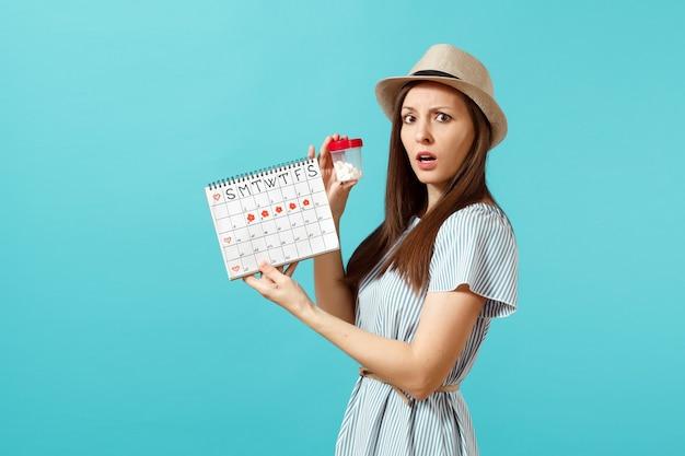 Porträt einer traurigen frau im kleid, die weiße flasche mit pillen hält, kalender für weibliche perioden, überprüfung der menstruationstage einzeln auf blauem hintergrund. medizinisches gesundheitswesen, gynäkologisches konzept. platz kopieren.