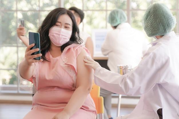 Porträt einer übergewichtigen asiatischen frau, die sich telefonisch bei einer covid-impfung in der klinik selbst fotografiert