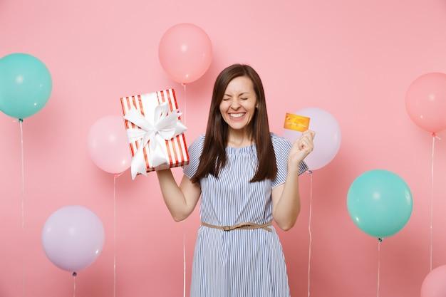 Porträt einer überglücklichen frau mit geschlossenen augen im blauen kleid halten kreditkarte und rote schachtel mit geschenk auf rosa hintergrund mit buntem luftballon. geburtstagsfeier, menschen aufrichtige emotionen.