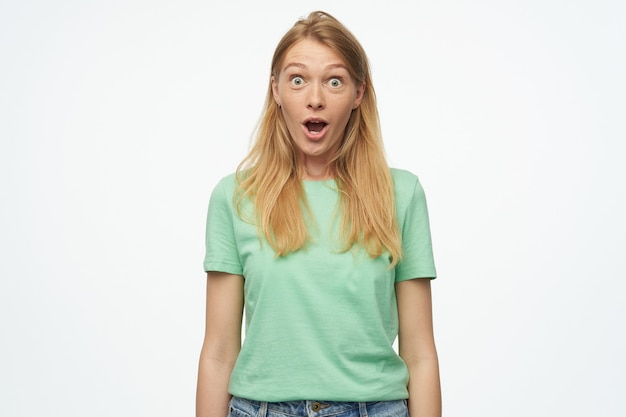 Porträt einer überraschten blonden jungen frau, trägt ein grünes t-shirt und starrt mit weit geöffneten augen und schockiertem gesichtsausdruck in die kamera