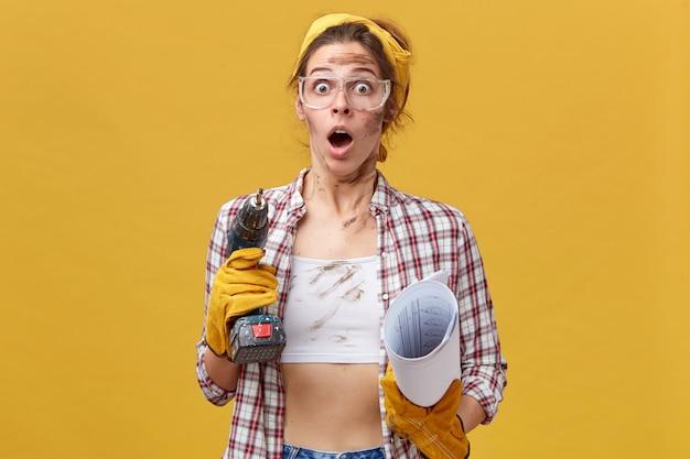 Porträt einer überraschten frau, die eine schutzbrille, ein kariertes hemd und ein weißes oberteil trägt, das bohrer und blaupause hält und nicht weiß, wie man bild repariert. erstaunte junge baumeisterin in freizeitkleidung