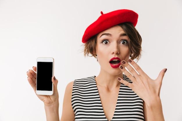 Porträt einer überraschten frau, die rote baskenmütze trägt