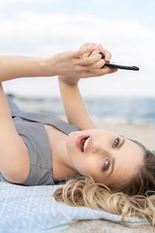 Porträt einer überraschten jungen frau, die ein handy hält und an einem strand liegt