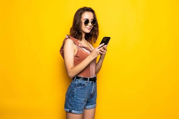 Porträt einer überraschten jungen frau im sommerhut und in der sonnenbrille unter verwendung des mobiltelefons lokalisiert über gelber wand