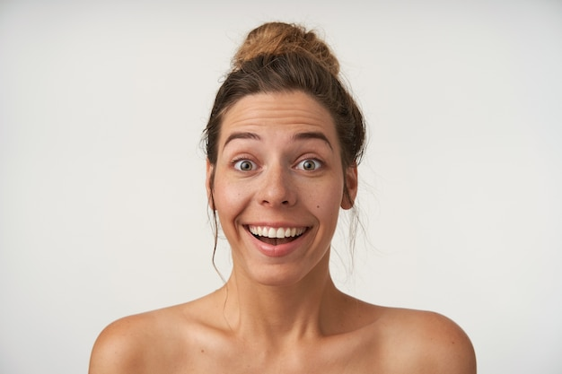 Porträt einer überraschten jungen hübschen frau mit lässiger frisur, die auf weiß mit hochgezogenen augenbrauen und erstauntem gesicht steht