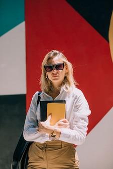 Porträt einer überzeugten blonden jungen geschäftsfrau, die gegen farbige gemalte wand steht