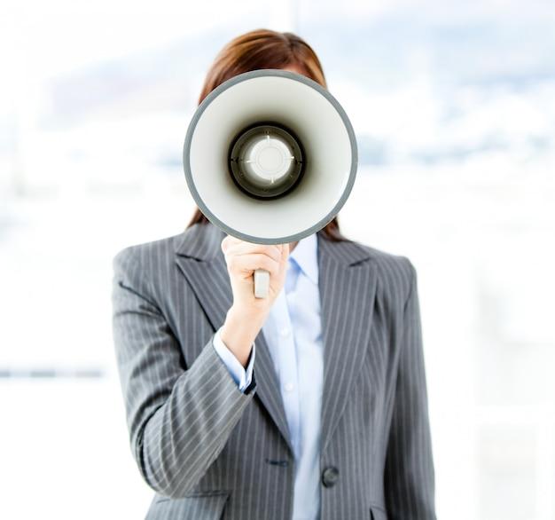 Porträt einer überzeugten geschäftsfrau, die ein megaphon verwendet