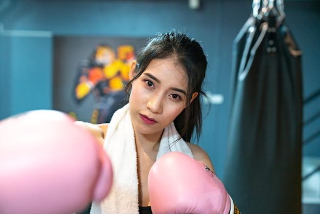 Porträt einer überzeugten jungen athletenfrau, die in den boxhandschuhen aufwirft