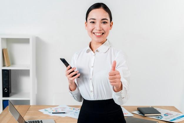 Porträt einer überzeugten jungen geschäftsfrau, die daumen herauf zeichen in richtung zur kamera im büro zeigt
