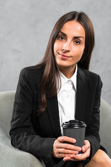 Porträt einer überzeugten jungen geschäftsfrau, die in der hand wegwerfkaffeetasse hält